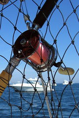 fishing reel, rod, and net, with blurred boats and water background