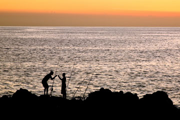 two Maui fisherman silhouetted at sunset